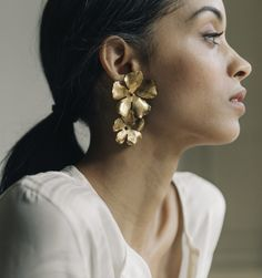 This bold, yet lightweight earring features two golden blossoms which frame the face for a natural, yet modern look. An easy way to dress up any outfit for day or night. We offer clip-on options of every earring style! To order please call Golden Earrings, Cluster Earrings, Unique Earrings, Flower Earrings, Statement Earrings, Stud Earrings, Flower Jewelry, Bridal Earrings, Fashion Earrings