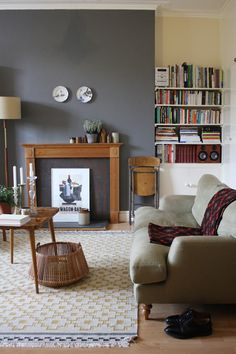 A slate grey is particularly attractive here with the wood furniture. Also, note to self: when you've got a great paint color, don't be afraid to put up small things on a big wall, as they have done here.