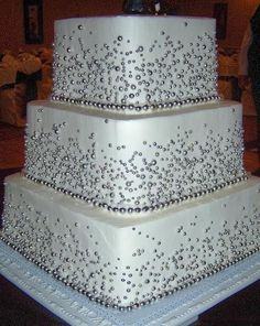 3 tier square with buttercream.  Covered with shimmering silver sugar pearls.  Serves 100
