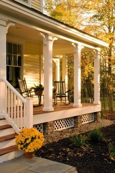 This is a fine traditional porch with beautiful Autumn leaves in the background.