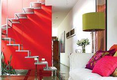 Cabos de aço sustentam a escada metálica, cujo desenho lembra um origami. A cor vermelha da parede valoriza ainda mais o ambiente