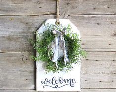 Darling Welcome wood tag with handmade wispy greenery wreath and bow color of your choice. Large wood tag measures 15 high by 9 wide and 3 4 thick. It is painted in white and distressed revealing wood grain underneath. Handmade little leaf greenery wreath Mason Jar Sconce, Hanging Mason Jars, Painted Mason Jars, Farmhouse Wall Decor, Rustic Wall Decor, Rustic Farmhouse, Rustic Chic, Greenery Wreath, Wreaths