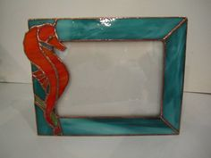 This stunning seahorse has his tail wrapped around seagrass on this beautiful picture frame. The frame holds a standard 5 X 7 photograph. This would make an incredible gift for anyone who loves seahorses or loves to dive. Glass Picture Frames, Picture Wall, Abstract Shapes, Geometric Shapes, Stained Glass Frames, Interior Design Themes, Incredible Gifts, Frame Stand, Oriental Design