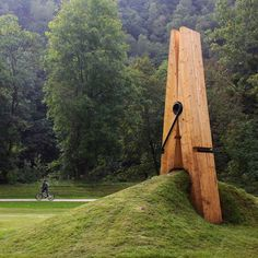 this giant clothespin sculpture by turkish artist mehmet ali uysal pinches the landscape in belgium.