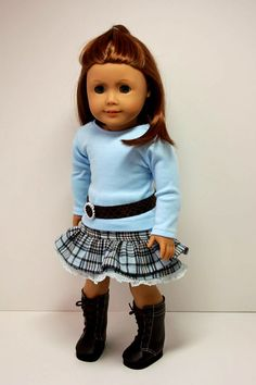 A great back-to-school ensemble for your American Girl's wardrobe. The light blue cotton knit tee has long sleeves and a back velcro closure. The ruffled skirt is blue and brown plaid and has an elastic waist. The belt is a brown faux alligator and has a velcro closure in the back.
