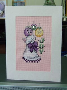 A cross stitch card which I made for my granddaughter -  pink and purple are her favourite colours and she likes white cats. I added the charms as extras.