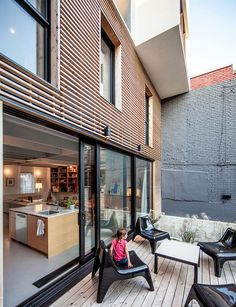 Small rear deck connected with the modern kitchen and living area of the Montreal home