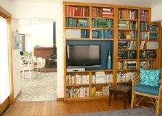 TV in a bookshelf. Idea of color coordinating the books seems like a horrible organizational scheme but really would make it easier to look at the Tv
