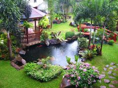exotic plants, pond with Koi fish and small bridge in the wonderful garden
