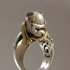 This beautiful piece of wearable art was designed and crafted by the artist and jewelry designer Sergey Zhiboedov (my husband). The ring was inspired by the style of the First French Empire, the early-19th-century design movement in architecture, furniture, and other decorative arts. It features two draped female figures. Made of sterling silver (the figures and the shank) and 14K yellow gold. Adorned with a genuine freshwater pearl (8.5-9mm diameter).