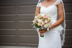 Romantic, whimsical bouquet of roses, lisianthus, flowering clethra and baby's breath