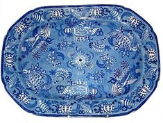 """""""Shells""""  This 18.25 inch by 13 inch platter is printed in medium to dark blue with stylized shells and sea plants. The border is also designed with shells and sea plants surrounded by an underglaze blue line at the edge. The maker is unknown. The platter dates from around 1830."""