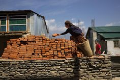Villagers work at rebuilding a year after the devastating earthquakes of 2015 in Barpak, in Gorkha district, Nepal, April 6, 2016.