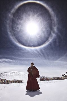 Tibetan Buddhist monk, prayer flags, and sun halo