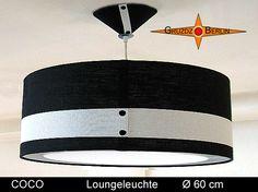 Loungeleuchte COCO als Ø 60 cm Pendellampe mit Diffusor und Baldachin. Klassik in Schwarz- Weiss mit plastischer Eleganz durch aufgesetztes Gitternetzgewebe. Im Stil der unvergänglichen Mode einer großartigen Designerin. Die Pendelleuchte COCO ist ein Hingucker und verleiht dem Raum Eleganz. Das schwarze Leinen wurde mit einem Streifen Gitternetzgewebe - batyline- besetzt. Dadurch tritt das Weiß optisch und plastisch hervor. Die zwei schwarzen Nieten setzen den besonderen Akzent.