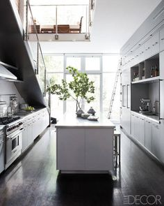 In the kitchen, stainless steel countertops and hand-painted cabinetry;  the range is by Wolf.    - ELLEDecor.com