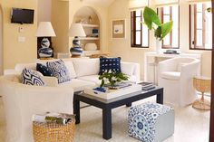 Cottage living room features a white sofa and chairs adorned with blue and navy pillows facing a navy coffee table and a blue ikat cube pouf alongside a sofa table topped with Bunny Williams Brush Stroke Lamp.
