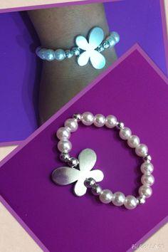 Perlas blancas con mariposa plateada en el centro.