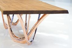 #G-Table K is made of copper bionic table construction and Kauri wood. Ancient Kauri is the oldest wood in the world while FiDU is the most innovative technology of flexible steel forming. Here the history meets the future.