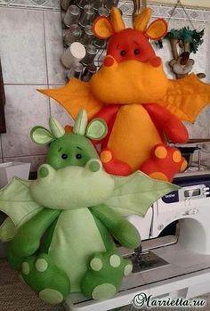 Large orange and green dragon stuffed toys.