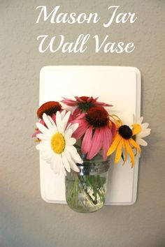 Step by step tutorial on how to make your own Mason Jar Wall Vase! Easy, inexpensive and you'll love the results! Pretty vase which is not in the way.