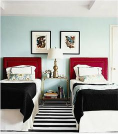 Twin beds, black and white rug, red headboard, pale turquoise wall