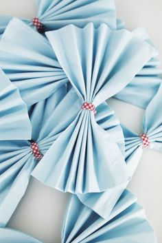"Paper napkins add a decorative touch to your tables for not a lot of money. Some are printed with pretty patterns and plain ones can be folded in fun ways. For example, fold napkins into pleats and tie them in the middle to create napkin ""bow-ties""."