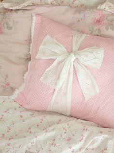 Adorable...  pink toss pillow with white lace ribbon tied around with bow.  Very sweet and simple.