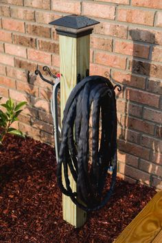 My finished garden hose organization and storage post with solar light looks great. Garden Posts, Garden Yard Ideas, Diy Garden, Lawn And Garden, Garden Projects, Deck Yard Ideas, Man Projects, Fence Ideas, Garage Ideas