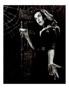 Vampira with a drink.
