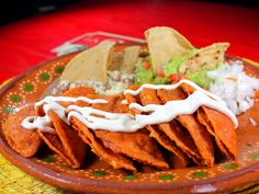 Las Enchiladas Potosinas llevan una masa preparada con chile rojo que les da su color. Estas van rellenas de una mezcla de queso fresco con chile y cebollita. Se sirven con crema fresca, lechuga en tiras y guacamole.