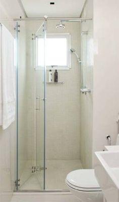 """Efeito sanfona. Os 3 m² deste banheiro impuseram aos arquitetos Lígia vailati e Diego romero, de São Paulo, o desafo de assegurar o máximo aproveitamento do boxe de 0,96 m². A dupla optou pelo kit box (conjuntode trilho e roldanas aparentes, da Atlanticbox) fechado com vidro temperado incolor com película desegurança. """"O vão abre totalmente mediante um leve toque"""", atesta a arquiteta. Pastilhas de vidro da vidro real."""