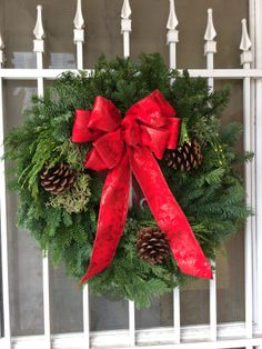 """JanLar 20"""" mixed wreath with a traditional red bow."""