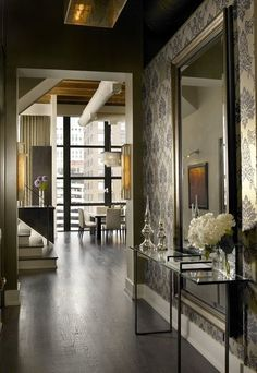 Wallpaper can be a great way to visually distinguish an open entryway from the rest of the house. The glass-top table provides a contemporary complement to the more traditional wallpaper pattern here.