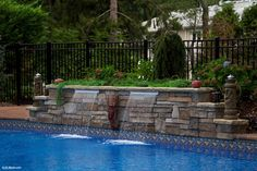 Raised Stone Wall with Sheer Descent Water Feature at new Vinyl Liner Pool Build. This water feature, along with several color changing LED key lights really make a statement all lit up at night!