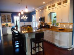 kitchen remodel, interior cabinet lights, recessed lighting, glass cabinet doors, stacked cabinets, quartz counter tops, wood floors, double oven, island, two- tier island, tile back splash, pendent lights