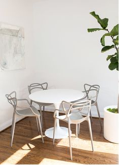 Contemporary dining space features a white Ikea Docksta Table surrounded by four gray Masters Chairs sat on wood floors holding a potted plant and contrasting white walls accented with a white and gray abstract art piece.