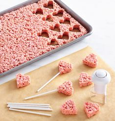 Add a little red food coloring to the marshmallows when making your basic crispy treats and stir until you get the desired pink color. Let the treats cool 10 minutes, cut out the hearts (about 35) and insert a lollipop stick in each.