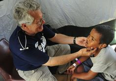 Project HOPE Volunteer Dr. Alan Jamison checking a young boy.