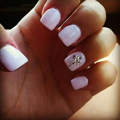 White nails with a simple jewled cross on ring finger.