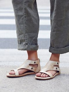 Soft, washed leather sandals featuring a padded sole for a comfortable fit. Open side cutouts and metal hardware. Exposed back zip for an easy on-off.