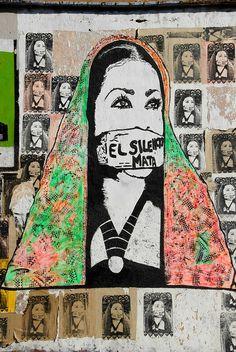 esto es una pintura de una mujer con una venda sobre su boca . dice que el silencio mata . Este pedazo del arte se encuentra en Oaxaca , México .