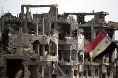 A general view shows the Syrian flag flying next to destruction in the Bab Amro neighbourhood of Homs on May 2 2012. (JOSEPH EID/AFP/GettyImages)