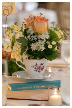 Tea cup centerpieces on book tops for a library wedding  www.myfloralimpressions.com Follow us on Facebook