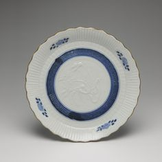 Circular dish of porcelain with lobed rim, decorated with central moulded design of birds and in underglaze blue with a band with key-fret pattern and four flower sprays: Japan, 18th-19th century,  K.2005.623