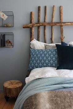 Driftwood headboard. Tree Stump nightstand. Metal Baskets as Shelves. Lace, velvet, linen, fur, fleece. Texture, texture, texture.