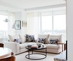 Living room with small sectional sofa. Round metal coffee table. http://cococozy.com