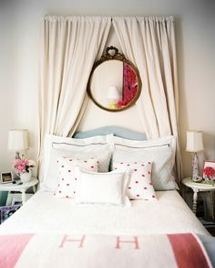 Mirror and curtains over bed.