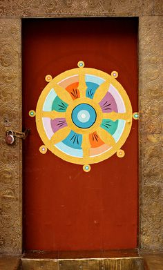 "Red door with dharma wheel or ""wheel of life"". Bhutan"
