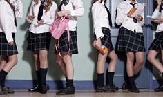Teenage schoolgirls standing in corridor, chatting in groups school uniform